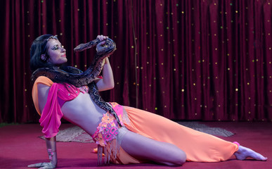 Female Snake Dancer Lying on Stage with Snake