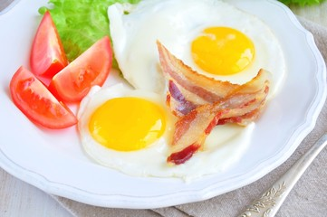 fried eggs with bacon and tomato slice on a white plate