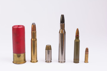 Variety of ammunition lined up and isolated on white.