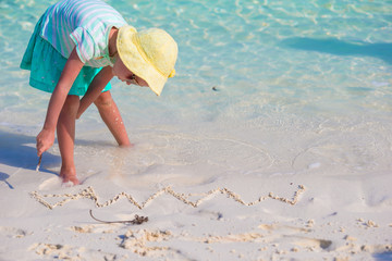 Little girl drawing on sandy beach