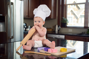 Toddler boy in a chef hat sitting in modern kitchen