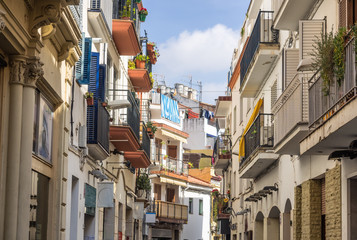 Narrow medieval street in Old Sitges, historical resort-city clo