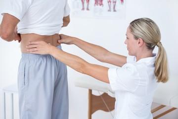 Doctor examining her patient back