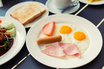 Ham breakfast served with coffee, toast and salads that taste go