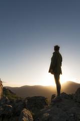 Mujer en lo alto de la montaña contempla el atardecer/Vertical