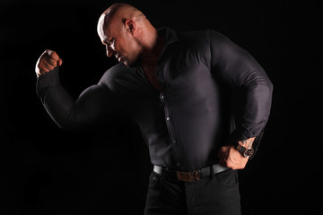 muscular bald man posing in a tight shirt on a black background