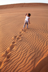 Baby - girl running in the desert.