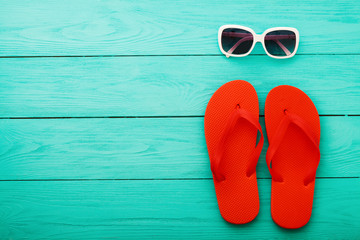 Red flip flops and sunglasses on blue wooden floor. Top view with copy space.