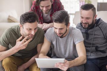 Group of men using digital tablet in living room
