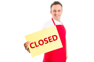 Supermarket male employee holding closed sign