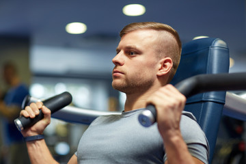 man exercising and flexing muscles on gym machine