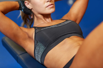 woman flexing abdominal muscles on bench in gym
