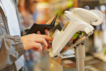 Man typing password at supermarket checkout