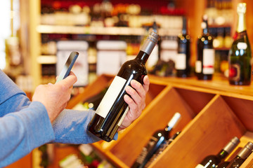 Hand with smartphone scanning wine bottle