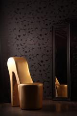 Goldener Schuhstuhl vor Ornamentwand und Spiegel