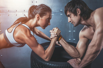 Athlete muscular sportsmen man and woman with hands clasped arm