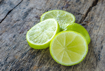Slices limes on rustic wood background.