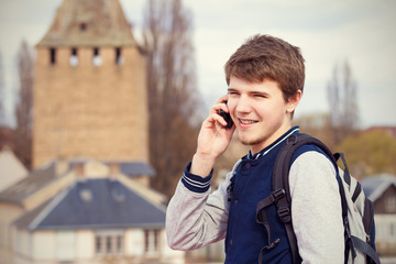 Smiling young man talking on mobile phone in a city