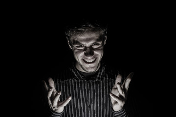 Man portrait with evil look isolated on black background.
