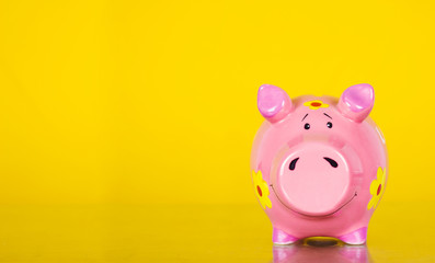 Piggy coin bank on yellow background
