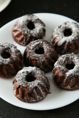 Chocolate bundt cakes on plate on black background
