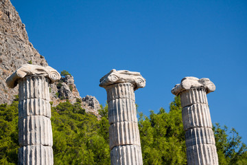 Three ancient columns background. Temple of Athena in Turkey