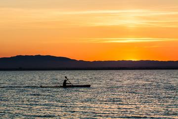 Man canoeing on sunset
