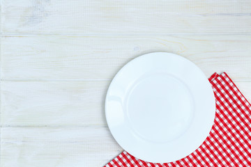 Empty plate and napkin on a white wooden background of a table.