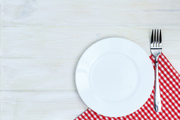 Empty plate and silverware over white wooden table background. V