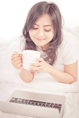 beautiful young woman hold cup of coffee lying think relaxing on
