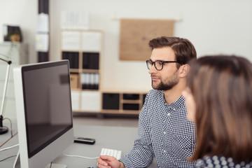zwei mitarbeiter im büro schauen auf computer