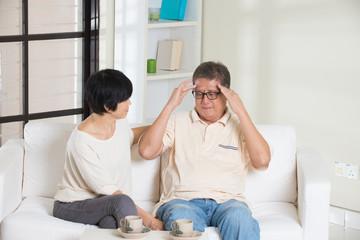 asian senior couple having headache