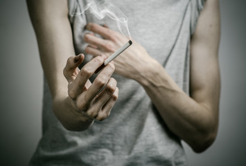 smoker holds the cigarette in his hand in the studio