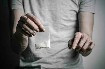 addict holding package of cocaine in a gray shirt  in the studio