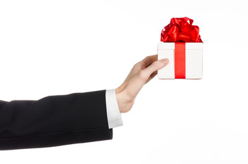 man in a black suit holding gift wrapped in white box in studio