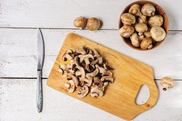 Sliced champignons on board and wooden bowl