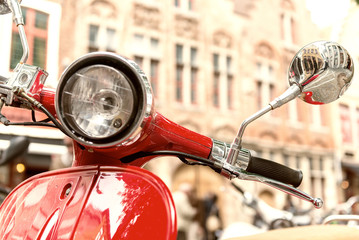 Fotorolgordijn Scooter Old fashioned red motorbike parked in city center