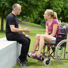 Frau im Rollstuhl im Park mit Freund