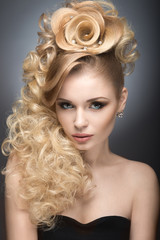 Beautiful blonde girl in evening dress with an unusual hairstyle in the form of roses and bright makeup. Beauty face. Picture taken in the studio on a gray background.