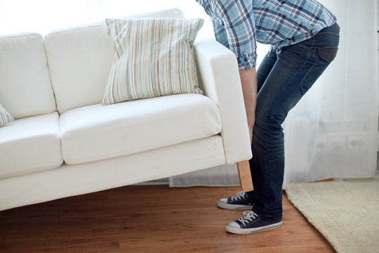 close up of male moving sofa or couch at home