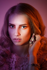 Beauty studio portrait of girl in pink dress with wavy hairstyle