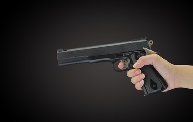 Hand holding gun isolated on black