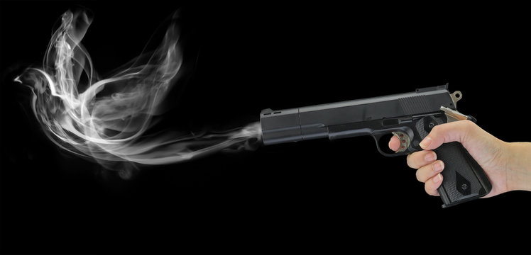 Hand holding a smoking gun isolated on black