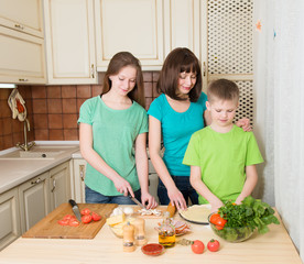 Teenager boy and girl with their mother cooking pizza at home.
