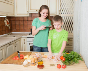 Children cooking homemade pizza at home kitchen. Making food photo.