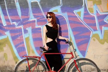 women in black dress and bike