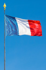 Vertical shot of flag of France waving in the wind with blue sky