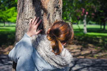 Woman hiding behind tree in park