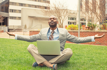 businessman with computer relaxing outside corporate office