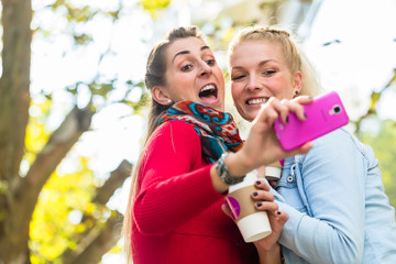 Freundinnen mit Kaffee und Handy in Stadt